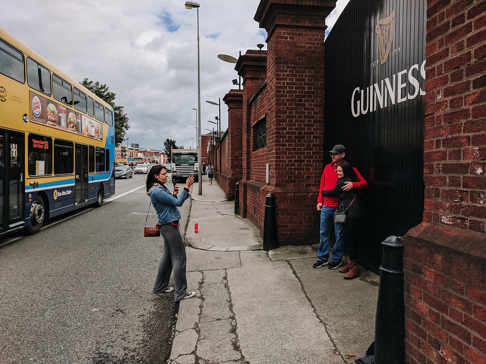 taking a photo of a couple in front of a guinness gate