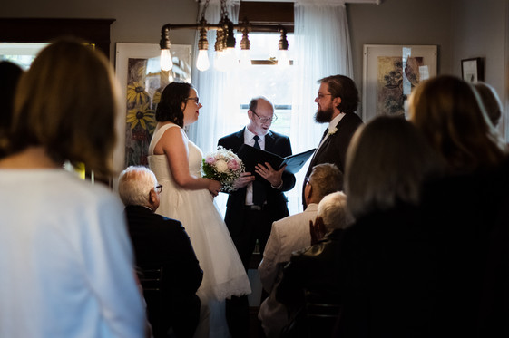 bride and groom saying vows in a intimate living room wedding