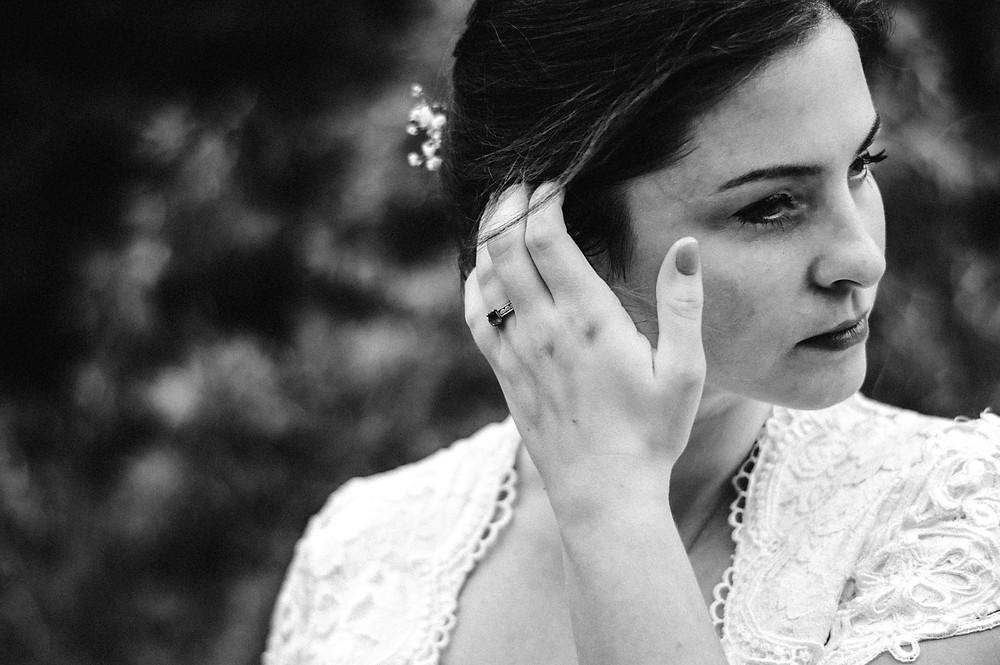black and white image of bride brushing hair aside