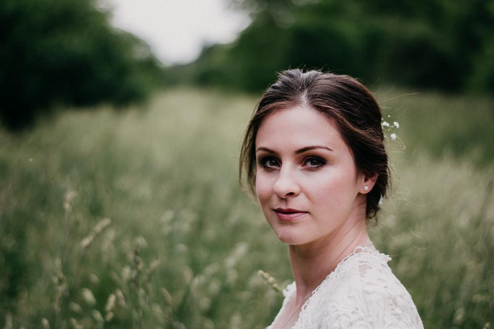 bride in wedding dress flowers in her hair in field