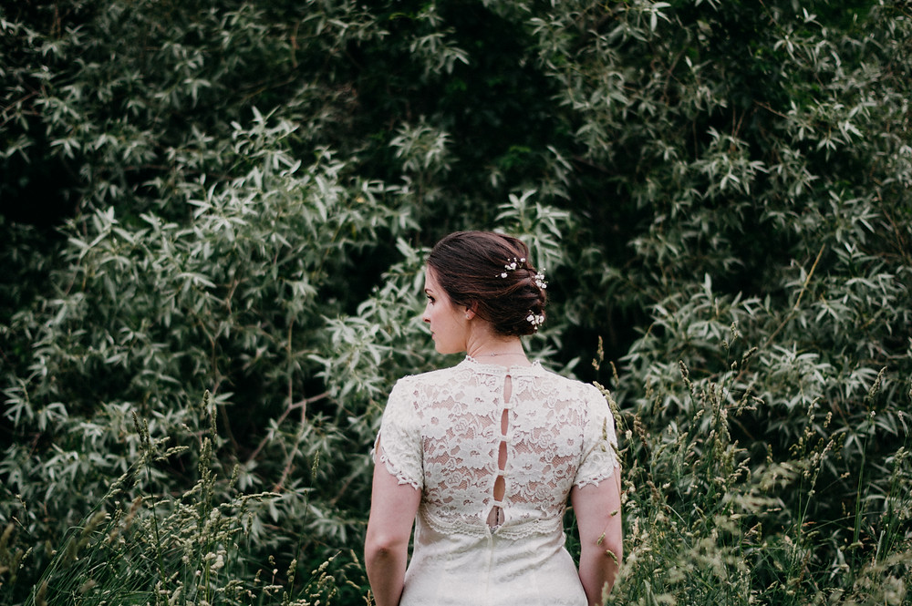 back of lace wedding dress in front of trees