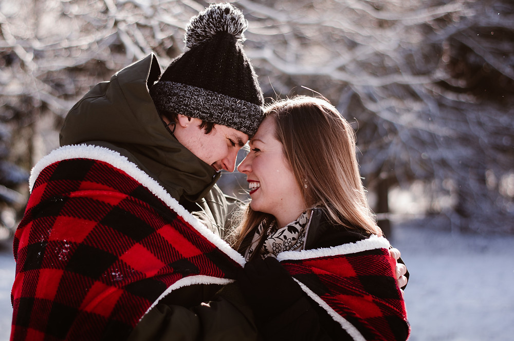 cute couple in buffalo plaid blanket winter photo session uofguelph arboretum