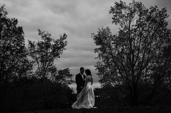 cinematic black and white bride and groom photo with trees and dramatic sky