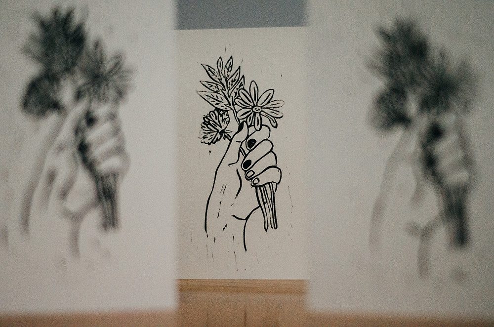 print of hand holding flowers