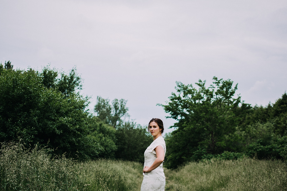 woman in wedding dress turning to look behind her in field