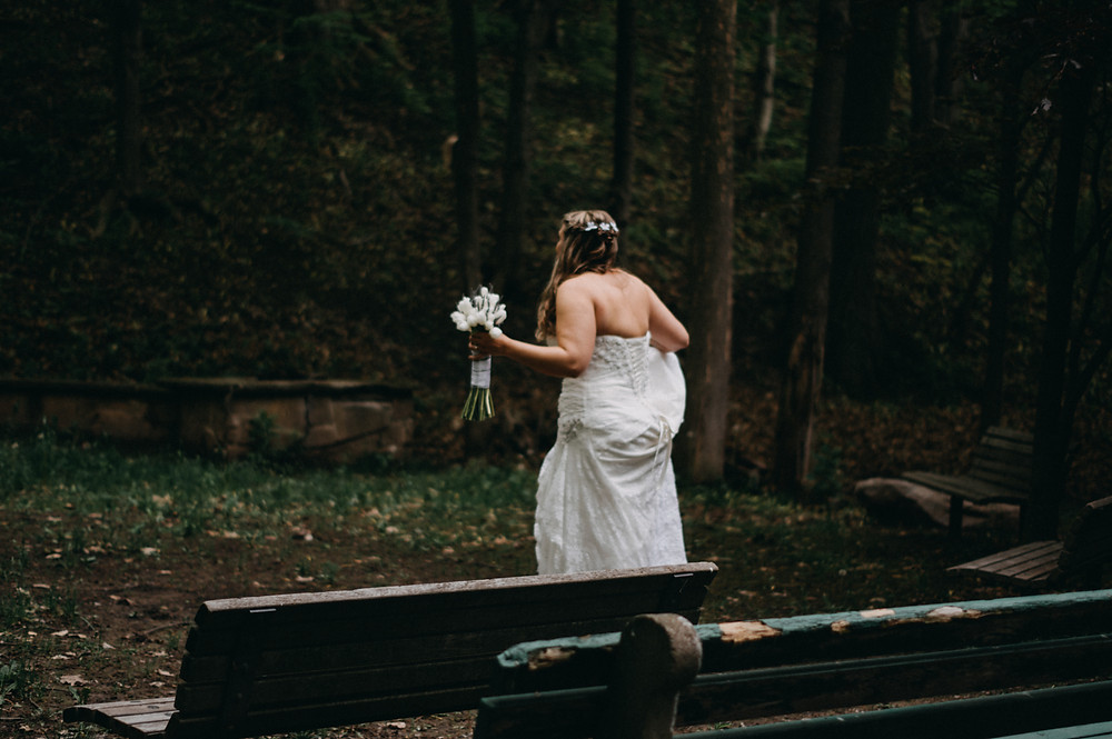 Bride walks through the woods while holding up her wedding gown