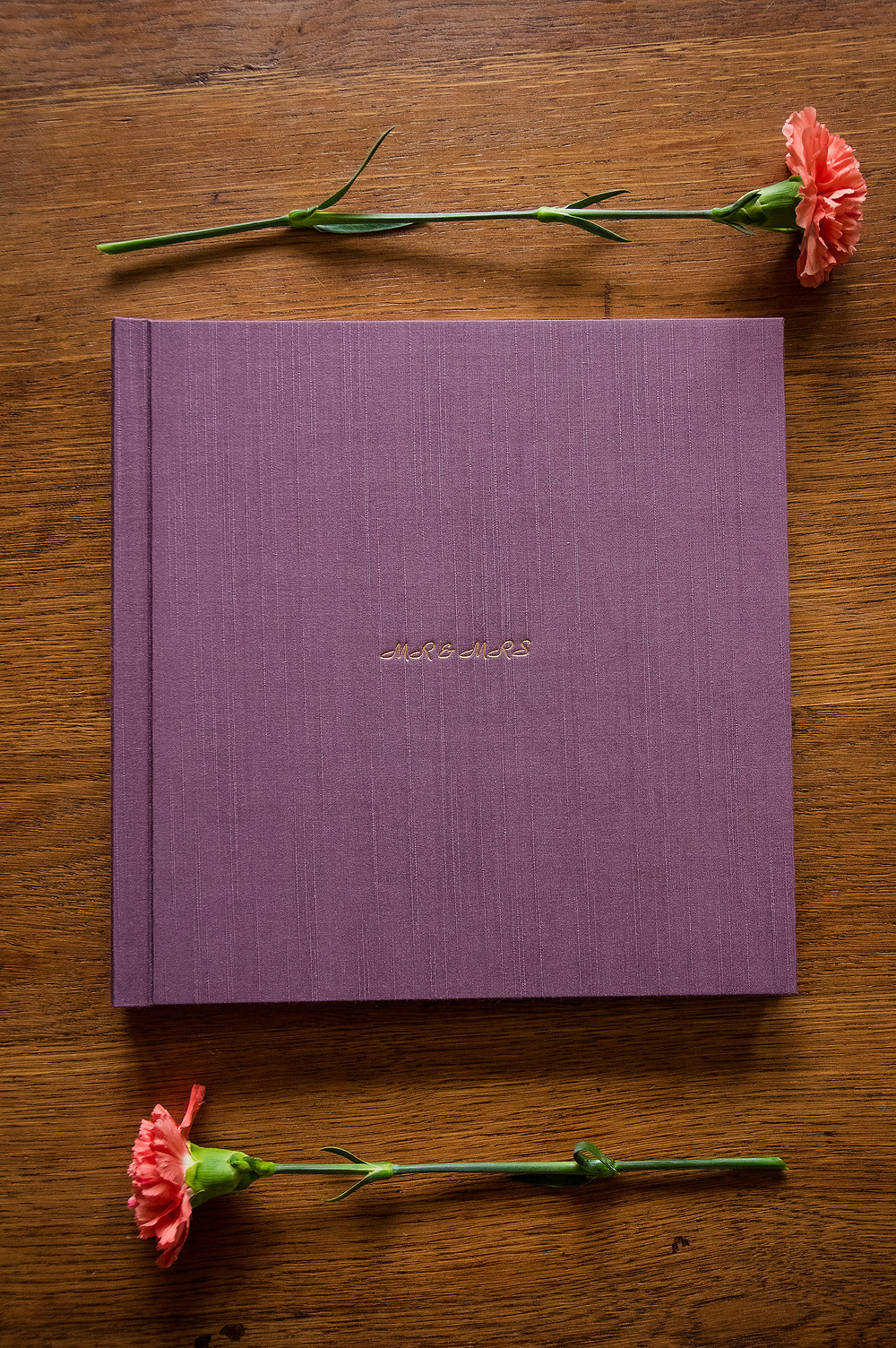 purple silk wedding album with pink carnations