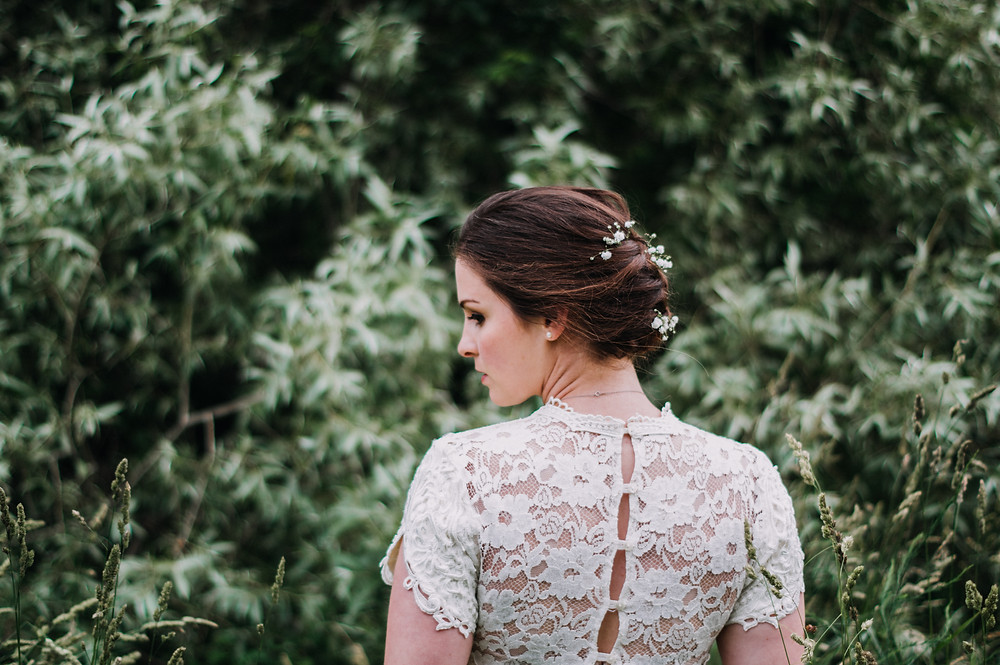 back of lace wedding dress braid and flowers in hair