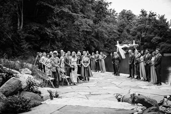 guests waiting for the bride at a ceremony by a pond