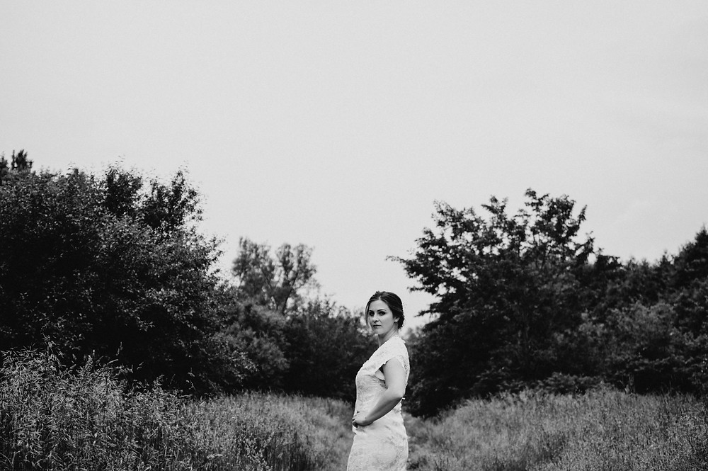 black and white image of bride turning to look behind her in forest