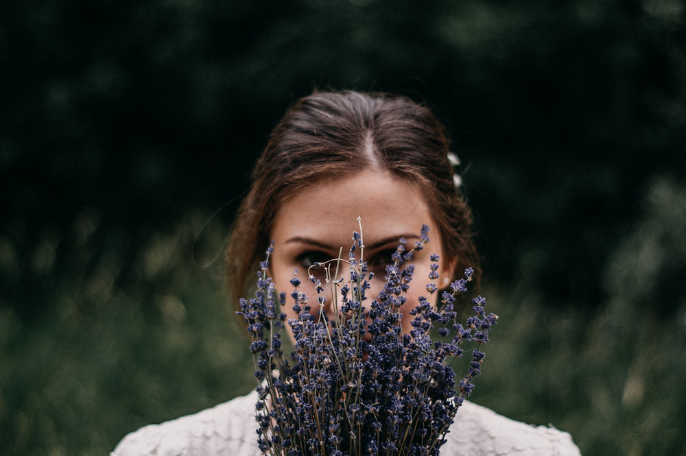 woman holding lavender in front of face