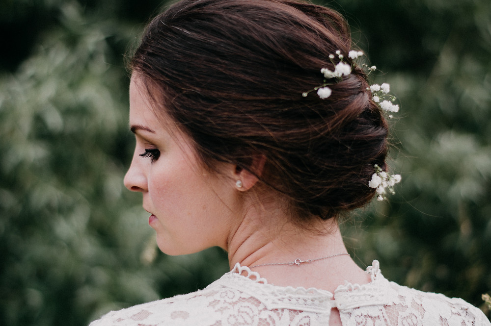 woman in lace dress braided hair with babys breath