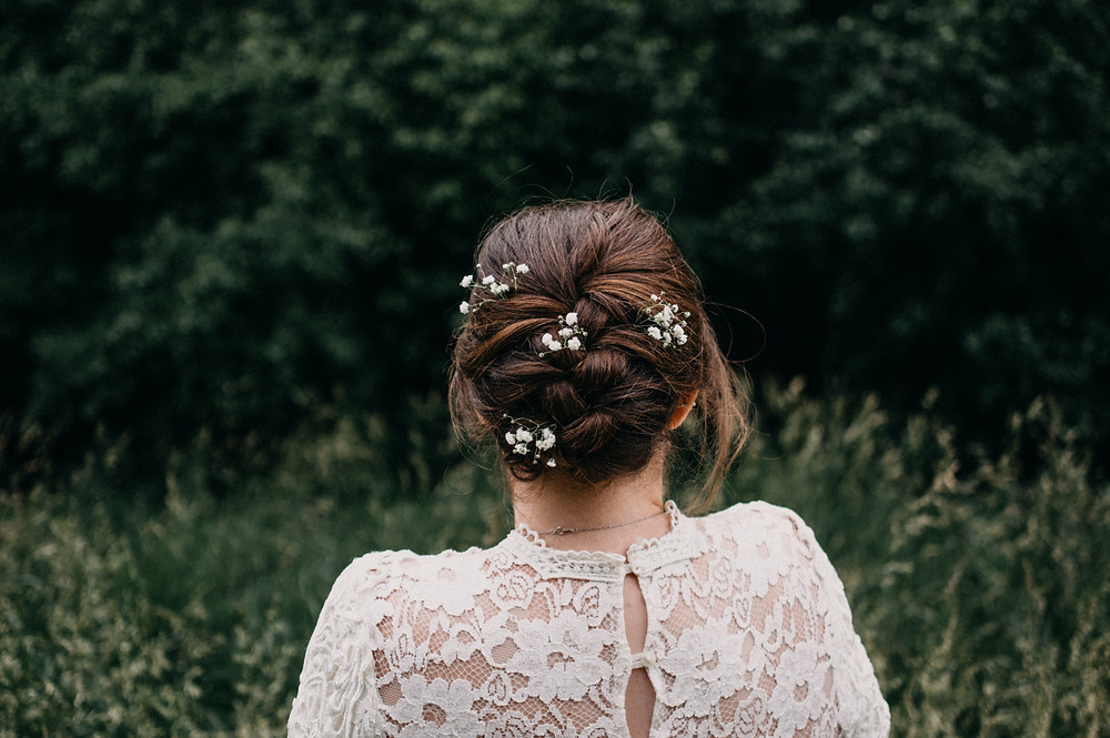 back of lace wedding dress flowers in hair