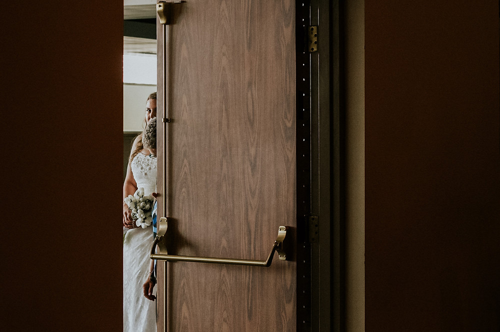 Bride peeking through the door waiting to go down the aisle