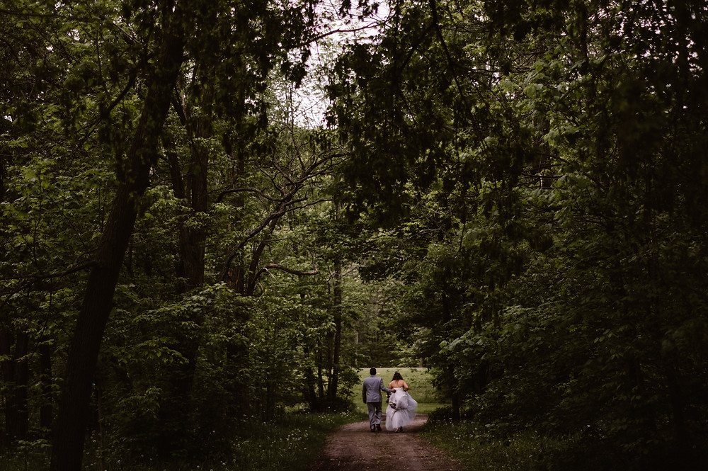 Bride and groom walking through the woods together at Sidrabene Camp and Retreat