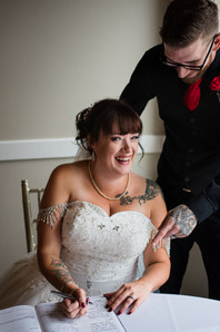 tattooed bride and groom signing the marriage licence