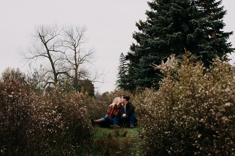 Sandy Ange Studios, Guelph engagemet photographer, fiance kissing in the bushes at the York Road Guelph Correctional Centre