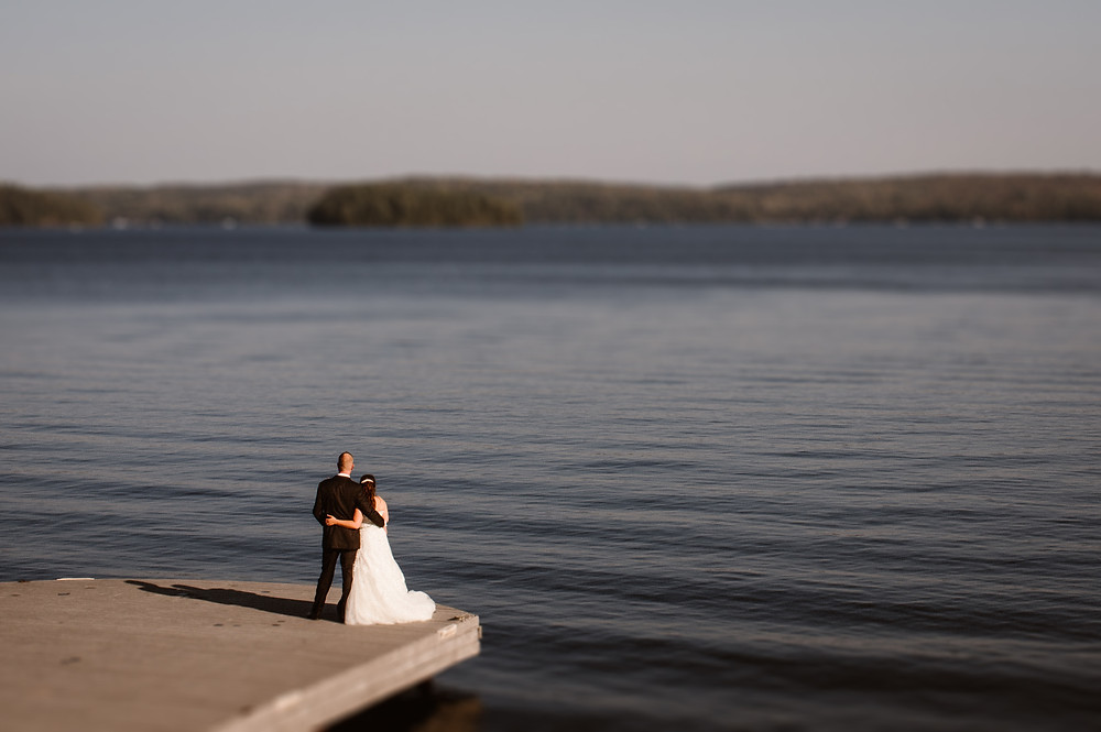 bride and groom standing on a dock looking out over a lake in muskoka ontario