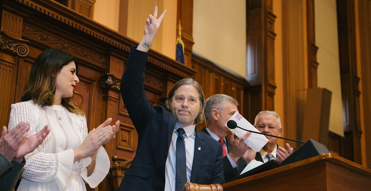 Tamlin Hall, flanked by wife Esti, House Chairman Randy Nix and House Speaker David Ralston, flashes the peace sign that has become emblematic of the Holden On film and movement. Photo by the Georgia House of Representatives Media Services
