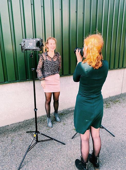 Evita fotografeert een jonge, witte vrouw voor een groene muur