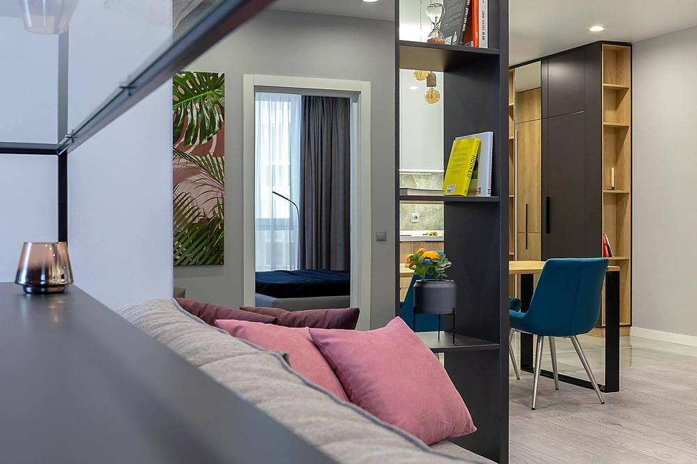 інтер'єр вітальні - диван, книжкові полиці, стіл