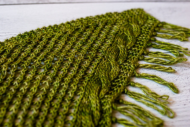 the corner of a mossy green hand-knit shawl done in a simple mesh stitch with a cable and fringe running along one edge.