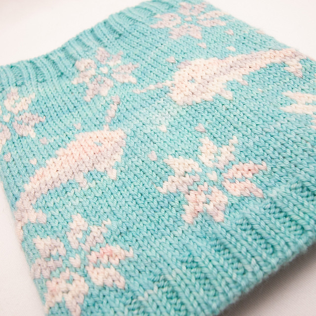 A blue and grey hand-knit colorwork cowl depicting narwhals and flowers.