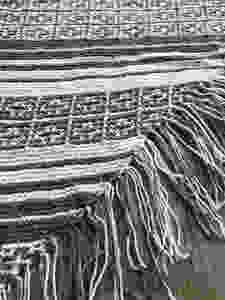A close-up of the geometric and striped patterning on the Magic Fringe Shawl
