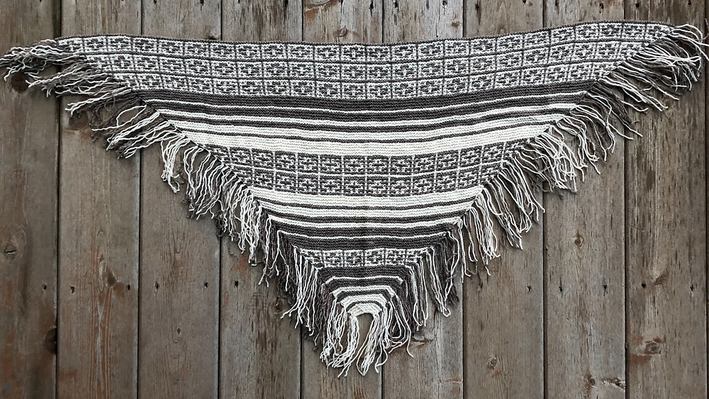 The Magic Fringe Shawl knitting pattern, a geometrical mosaic knitted triangle shawl with a dramatic fringed edging that utilizes fingering weight yarn