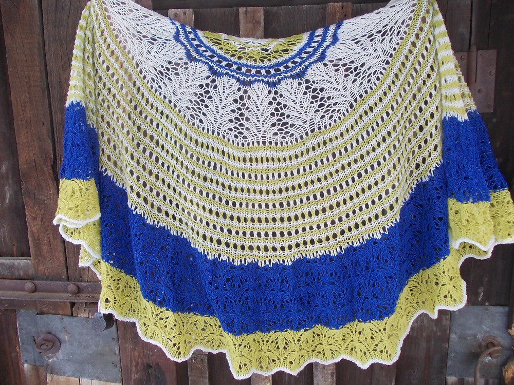 A gorgeous blue, white and yellow version of the I Guess That's Why knitted lace shawl.
