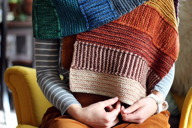 Multi-colored, hand-knit wrap in gradient color scheme.