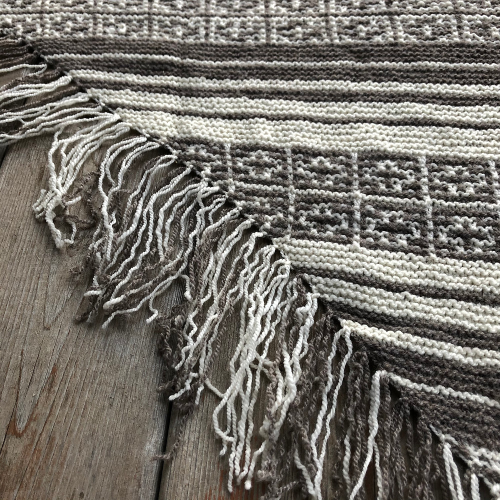 Natural colored two-tone hand knit shawl with fringe and a geometric patterning.