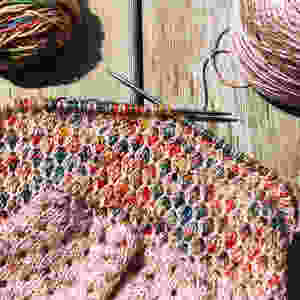 A mosaic and eyelet shawl is being knit from 2 different skeins of yarn