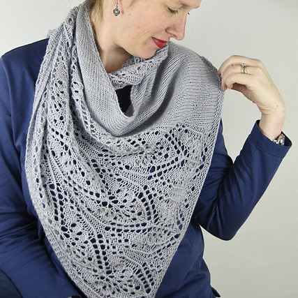 A beautiful medium grey hand-knit shawl with a cascade of lace patterning running along 1 side.