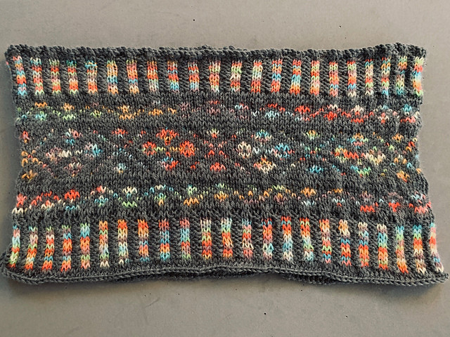 A grey and multi-colored color-work, hand-knit cowl