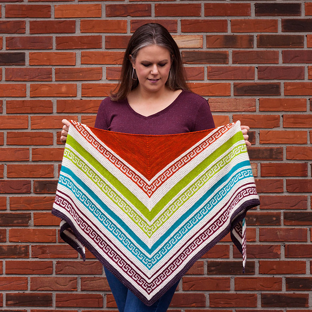 A woman looks down towards the hand-knit multi-color triangle shawl that she's holding. The shawl features white, orange, green, blue, & purple stripes along with a mosaic Greek Key pattern.