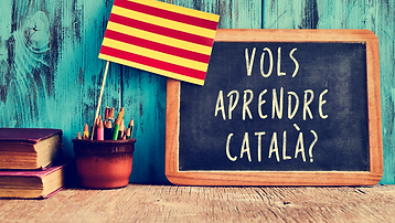 Aprendre català en família, bandera catalana, pissarra i pregunta: vols aprendre català?