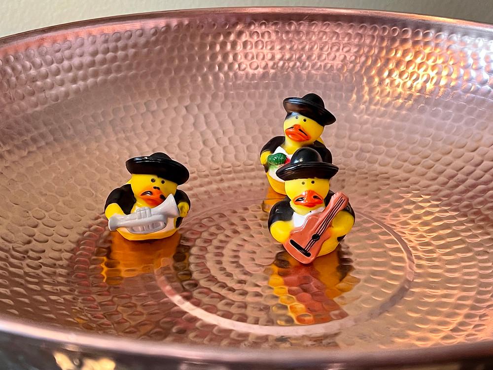 3 mariachi ducks inside a copper rain chain basin