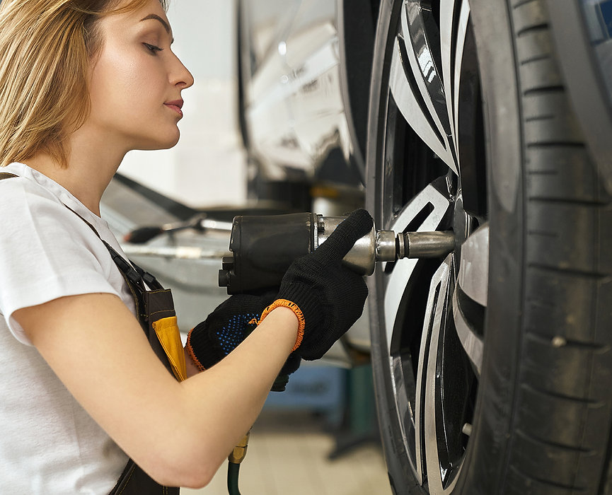 side-view-of-female-mechanic-changing-tire-of-auto-M3L5PN2.jpg