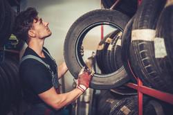 professional-car-mechanic-choosing-new-tire-in-aut-PN5QEWT