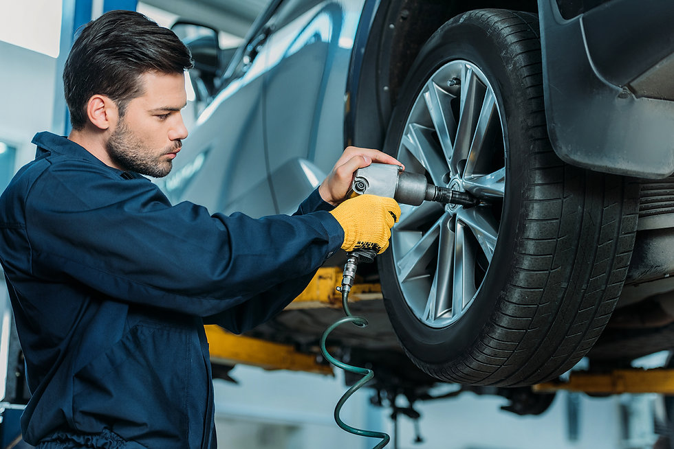 automechanic-unscrewing-tire-bolts-on-a-lifted-up--4LECAZJ.jpg