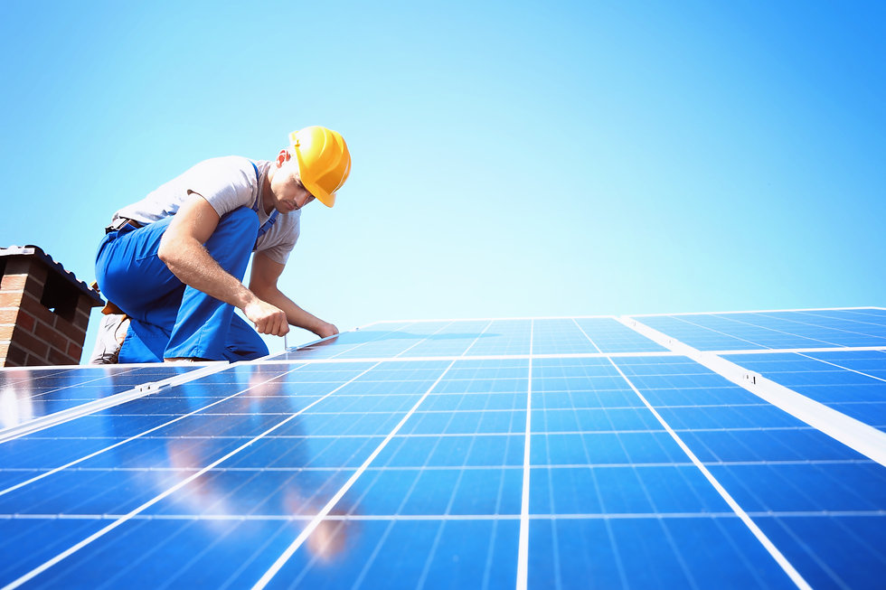Worker installing solar panels outdoors.