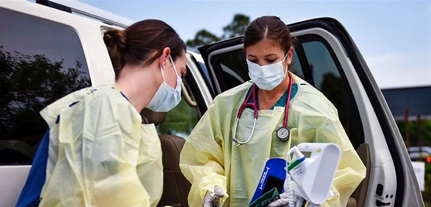 Two medical professionals prepare for patients at a COVID-19 Drive-Up