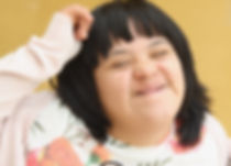 Young woman with down syndrome stroking her hair while laughing