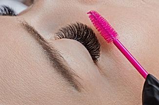 Eyelash extension procedure. Woman maste
