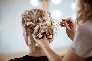 Female hairdresser making hairstyle to b
