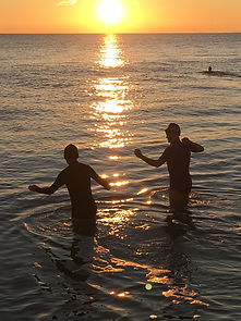 Swimmers entering the sea with sunset
