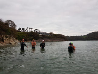 Swimmers standing in shallow water