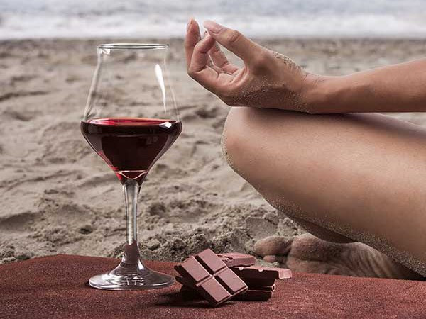 Red wine and chocolate next to a woman practising yoga on a beach