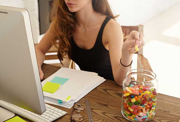 Woman working at a computer and eating jelly sweets